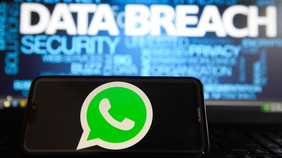 In this photo illustration, the Whatsapp logos is seen on a Huawei smartphone with the word Data breach on a laptop monitor
