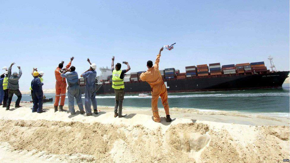 Egytpian workers wave towards a Container ship sailing on the waterway of the New Suez Canal on 25 July, 2015
