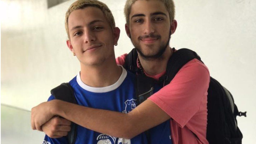 Two teenage boys hug each other and grin broadly
