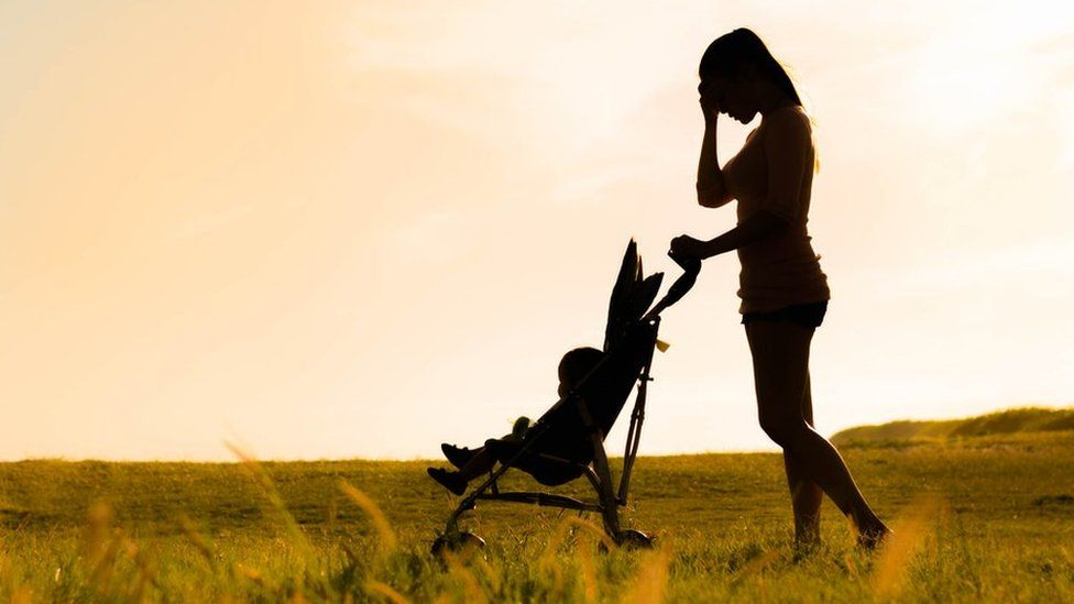 Mother with child in pushchair in field