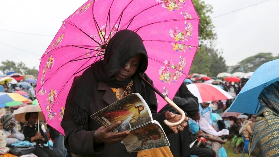 Woman prays under umbrella