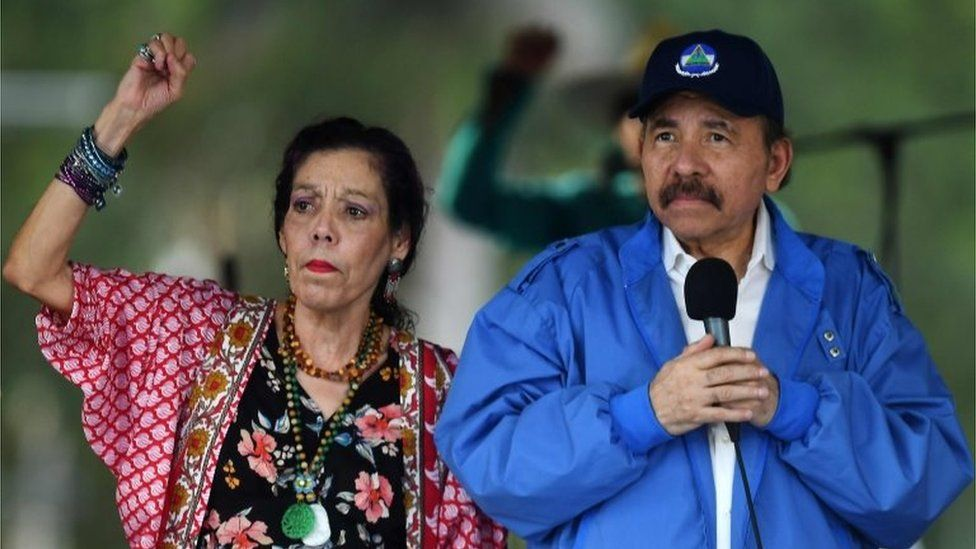 """Nicaraguan President Daniel Ortega (R) and his wife, Vice President Rosario Murillo, cheer at supporters during the government-called """"Walk for Security and Peace"""" in Managua on July 7, 2018. A"""