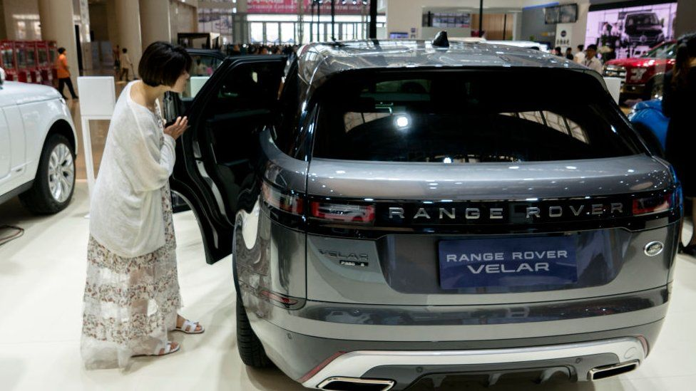 A woman looks at a Range Rover in a car dealership in China