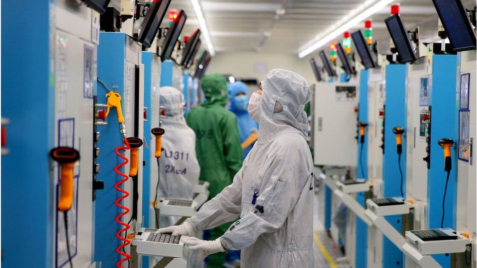 Employees work on the production line of silicon wafer at a factory of GalaxyCore Inc. on May 25, 2021 in Jiashan County, Jiaxing City, Zhejiang Province of China.