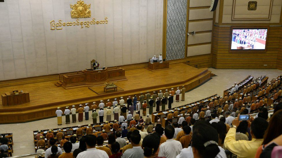 New Myanmar Ministers including the country's democracy icon Aung San Suu Kyi (front row 9th R, in blue) are sworn into office by Upper House Speaker Mahn Win Khine (on podium) during a ceremony at the parliament in Naypyidaw on March 30, 2016.