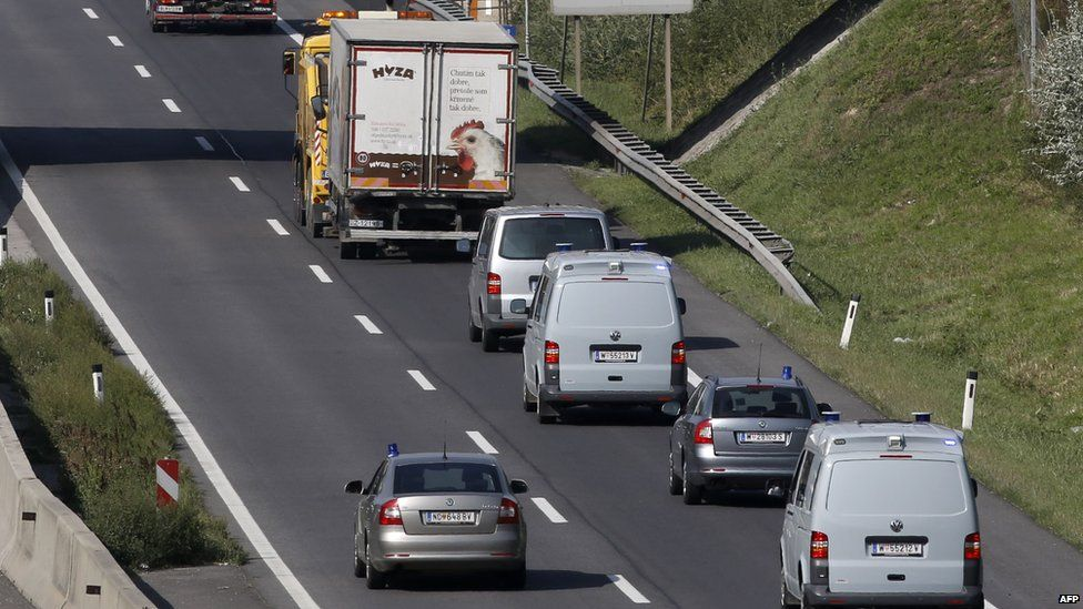 A convoy of police vehicles follow a refrigerated truck being towed along a highway near Neusiedl am See, Austria (August 27, 2015)