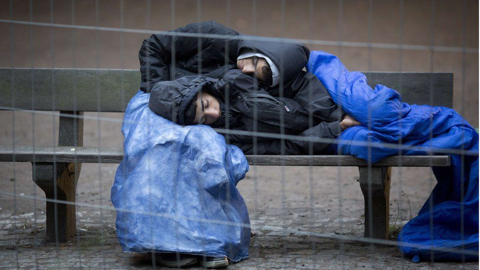 Two refugees sleep on a bench on the grounds of the State Office of Health and Social Affairs (LAGeSo) in Berlin on 9 October 2015, where they wait for their registration.