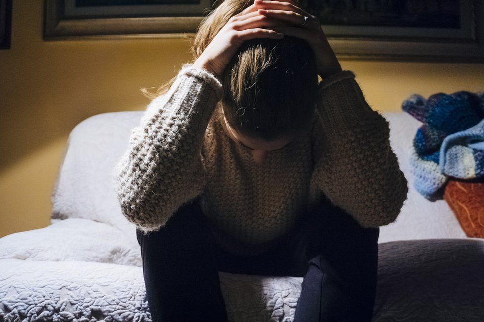 Woman sat on bed looking sad