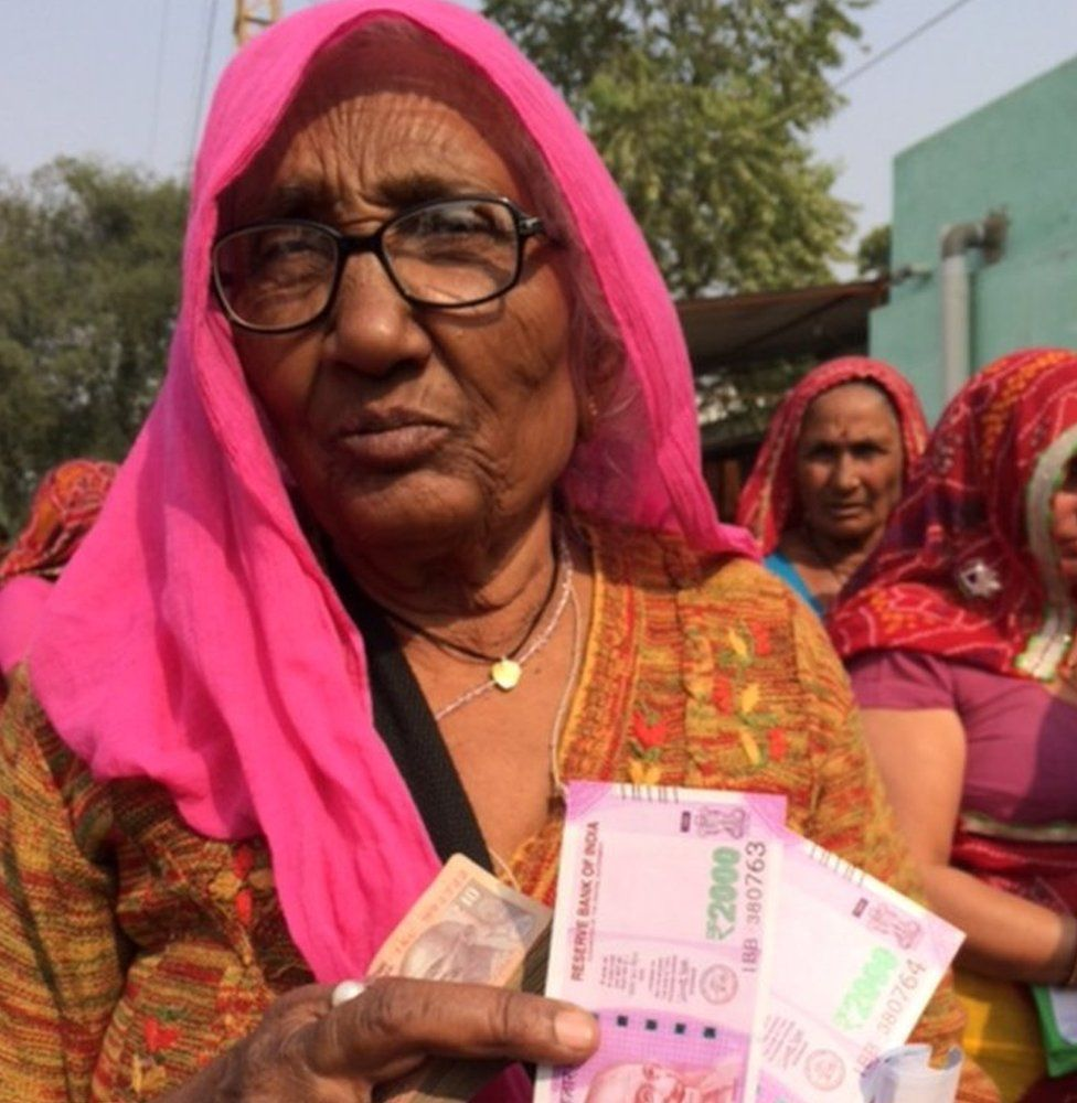 A woman displays some of the new notes