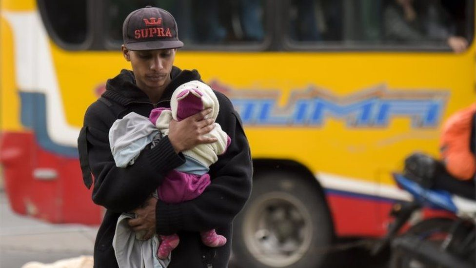 A Venezuelan migrant carries a baby at an improvised camp near a bus terminal in Bogota on September 11, 2018.