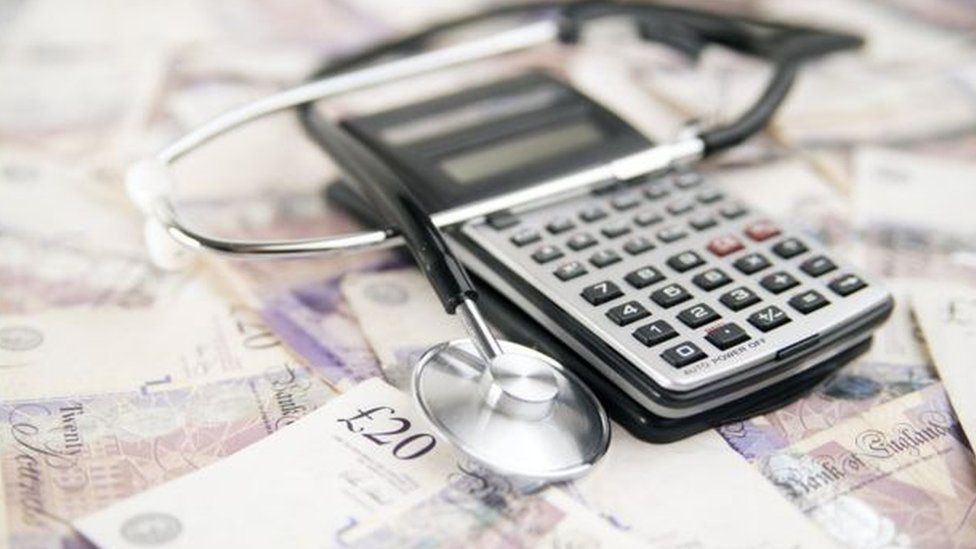 image of calculator, stethoscope and money