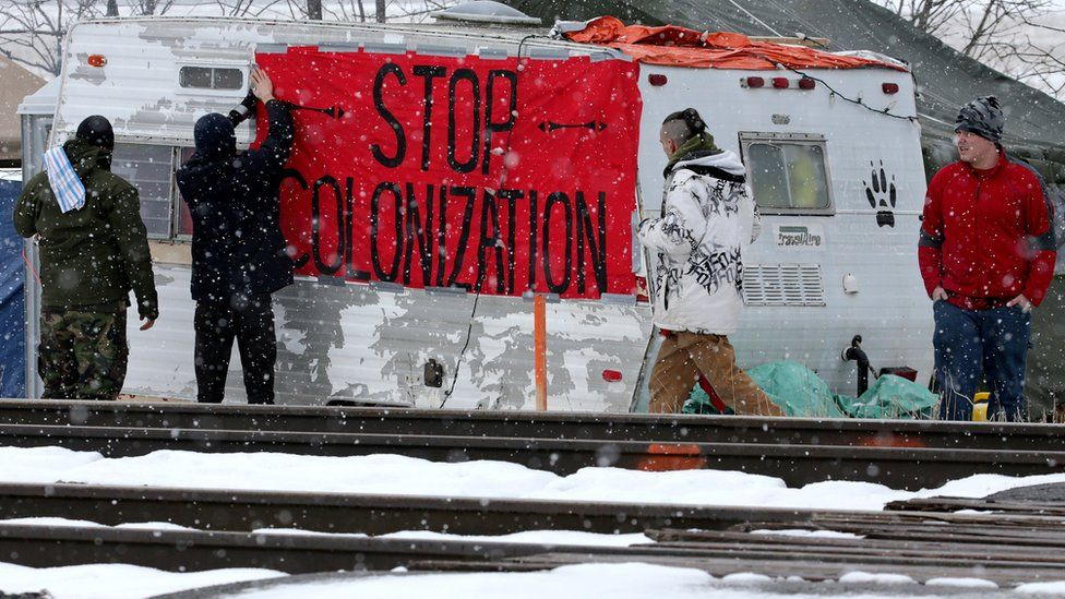 First Nations members of the Tyendinaga Mohawk Territory place a sign at a blockade of train tracks