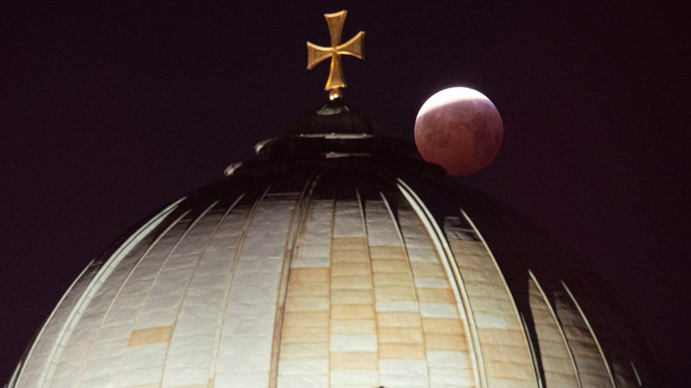 7 A view of the lunar eclipse over the cross on top of the Elizabeth Church in Nuremberg, Germany, 21 January 2019.