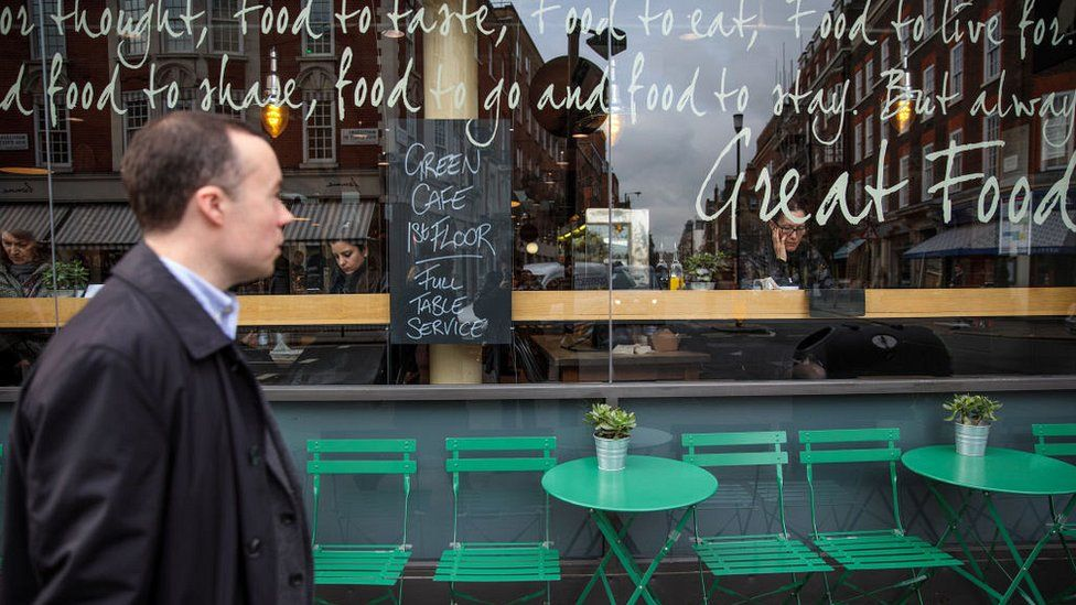 Man walks past cafe
