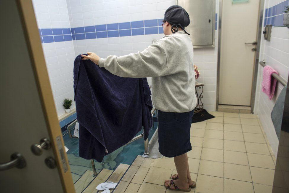 A Balanit, or mikveh attendant holds a towel for a Jewish woman who entered the water of a mikveh in Jerusalem on April 17,2019. (Photo by Heidi Levine for The BBC).