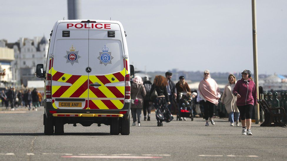 A police van patrols on the promenade next to Brighton Beach, East Sussex.
