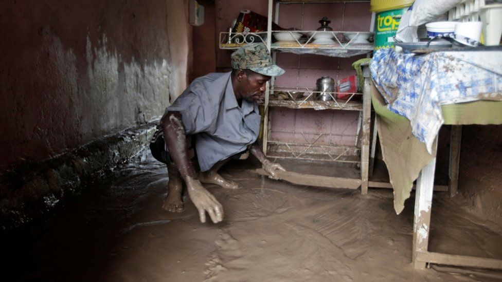 A man clears water from his room in Les Cayes, Haiti, on 5 October 2016