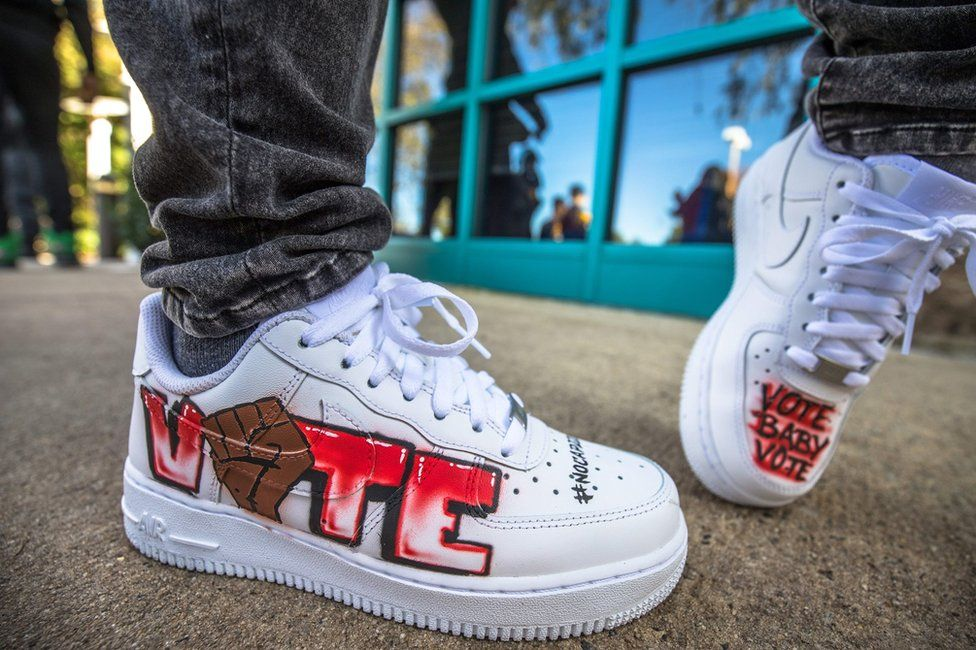 A pair of shoes with voting messages drawn on