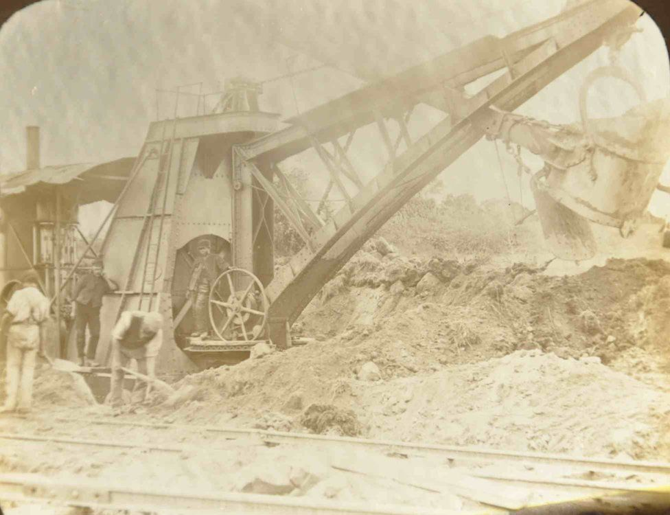 Steam engine workers Mugdock showing workers using a large steam-driven trencher for digging trenches