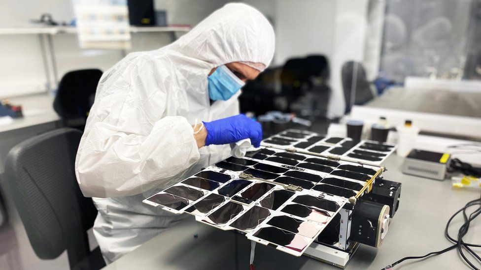 A NanoAvionics engineer assembling a nanosatellite