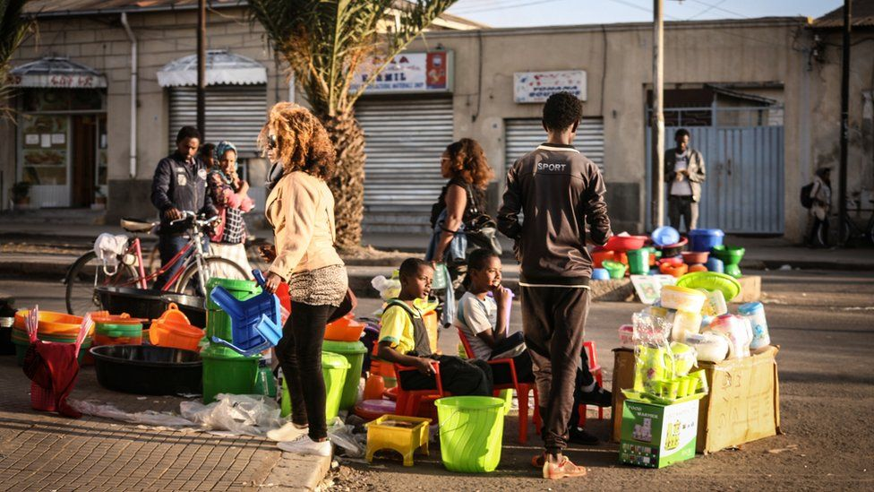 People and someone with a bicycle walking past a street stall selling tupperware in Asmara, Eritrea