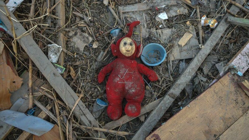 Childrens toys in the rubble of houses