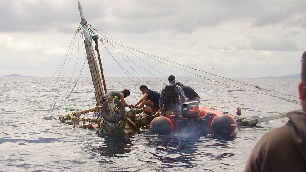 In this photo provided by the Philippine Coast Guard, members of the Philippine Coast Guard inspect the almost sunken fishing boat of Filipino fishermen who were killed by suspected pirates in waters near Zamboanga City, southern Philippines on 10 January 2017.