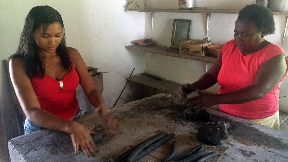 Two women working in the pottery cooperative