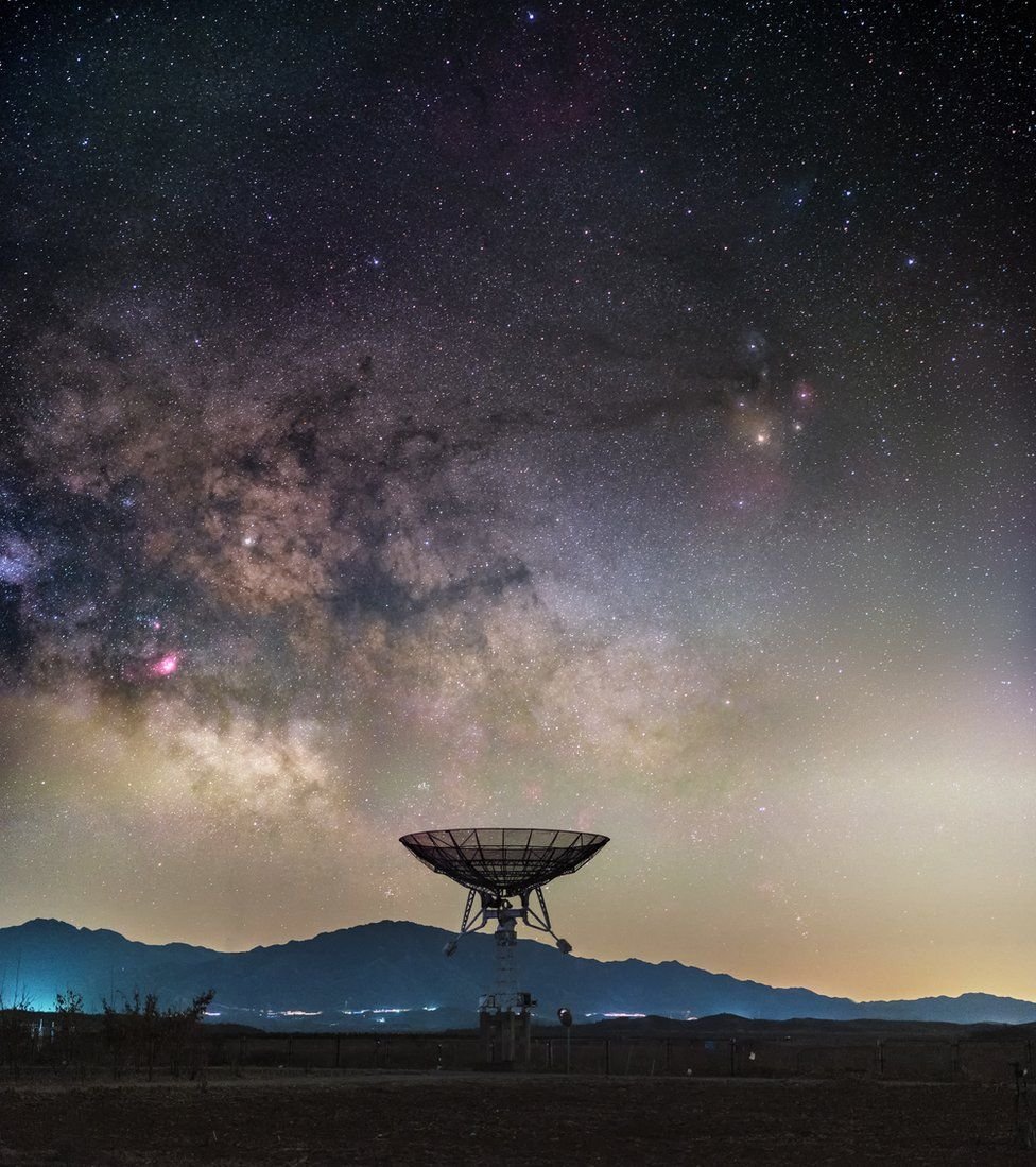 The Milky Way rises ominously above a small radio telescope