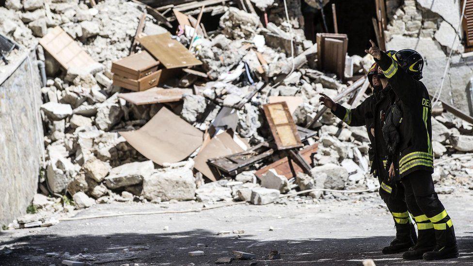 Fire crews stand near rubble in Arquata, Italy