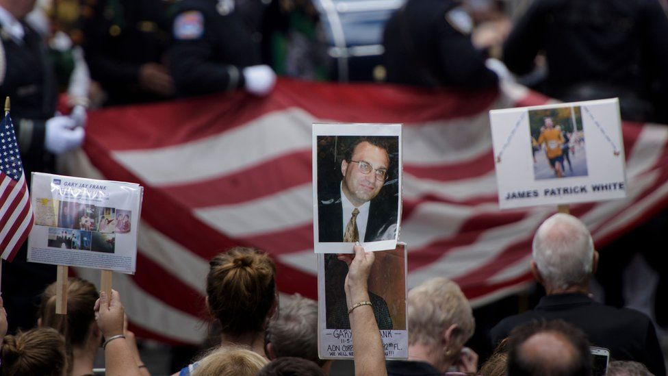 People hold up photos of victims during a memorial service at the 9/11 memorial on in New York.