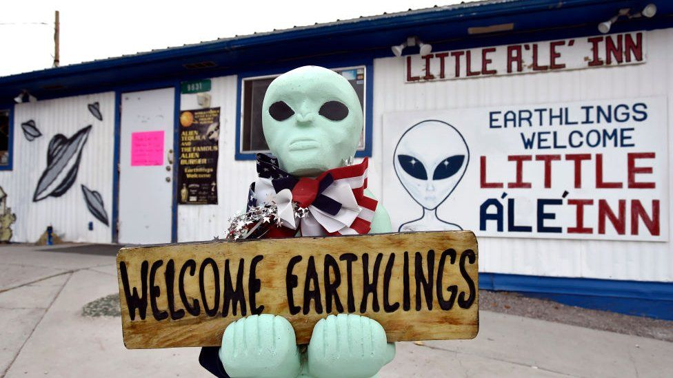 An alien-like statue displays a sign welcoming guests to the Little A'le' Inn restaurant and gift shop in Rachel, Nevada