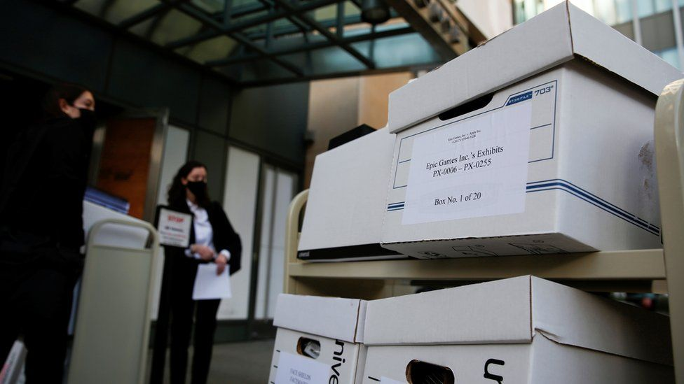"""Boxes of documents wait outside a court building under guard - one label reads """"Epic Games Inc's exhibits, box 1 of 20"""""""