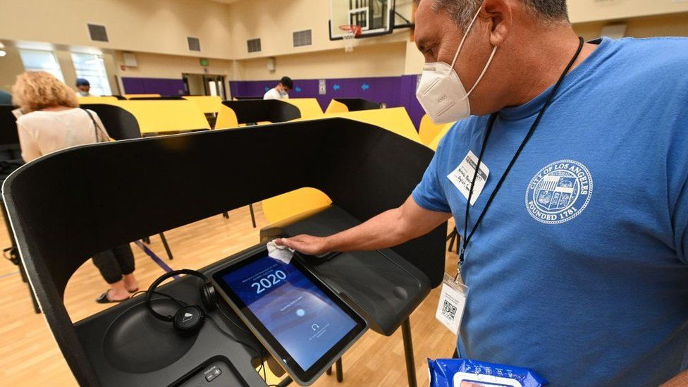 Poll worker cleans voting machine