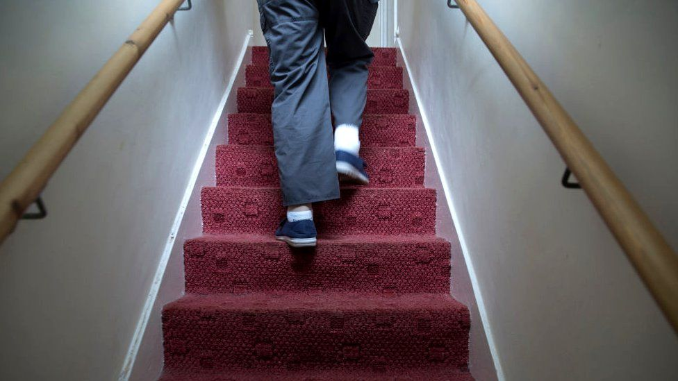 A man walking up stairs in a house
