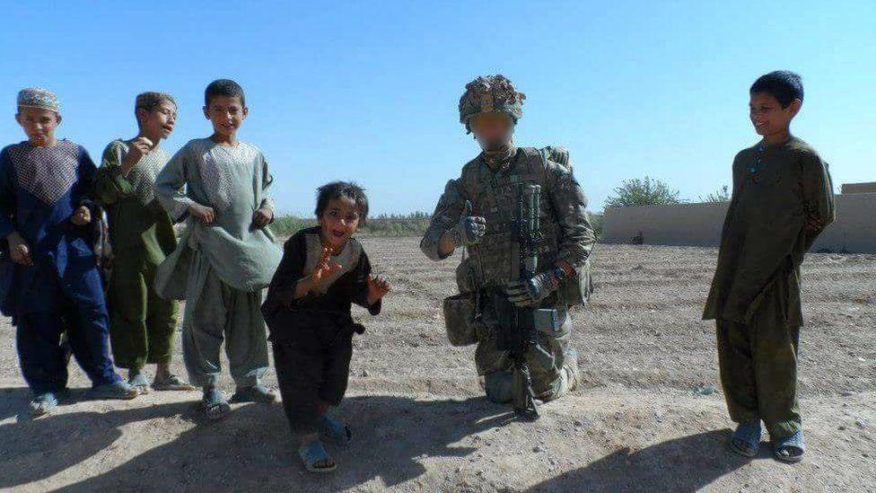 Ben Baker in combat gear with Afghan children