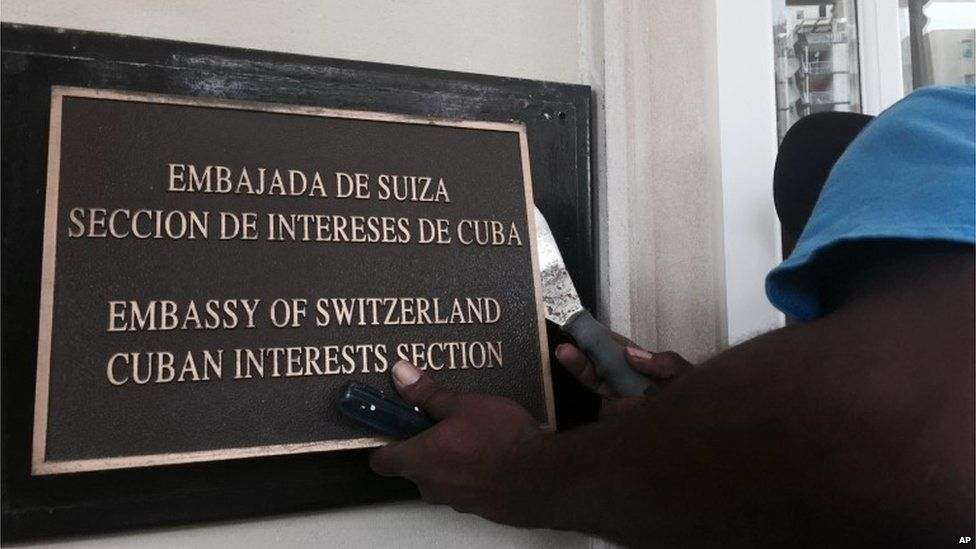 A worker removes the Cuban Interests Section sign in Washington, just days prior to the building being accredited as the Cuban Embassy (15/07/2015)