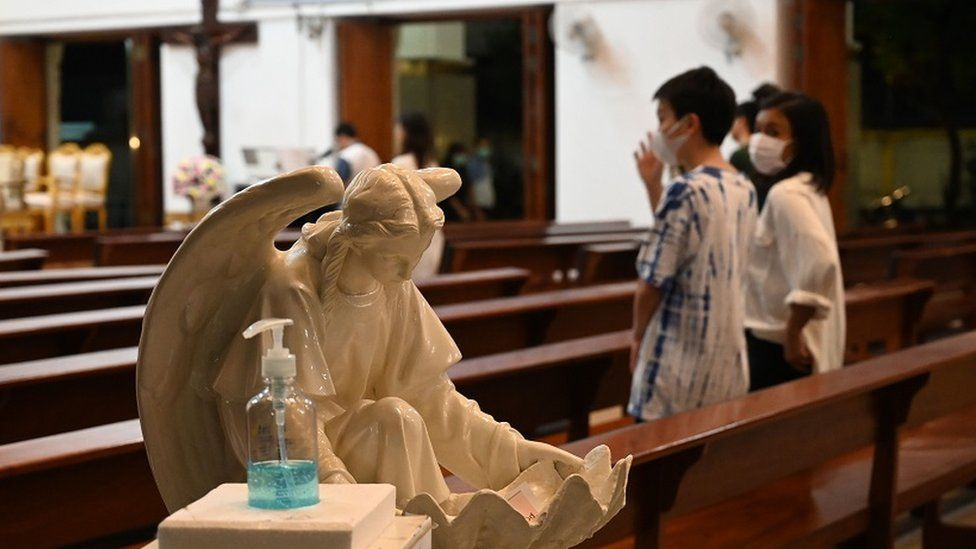 A bottle of hand sanitizer at the entrance of a church in Bangkok, with worshippers wearing face masks in background