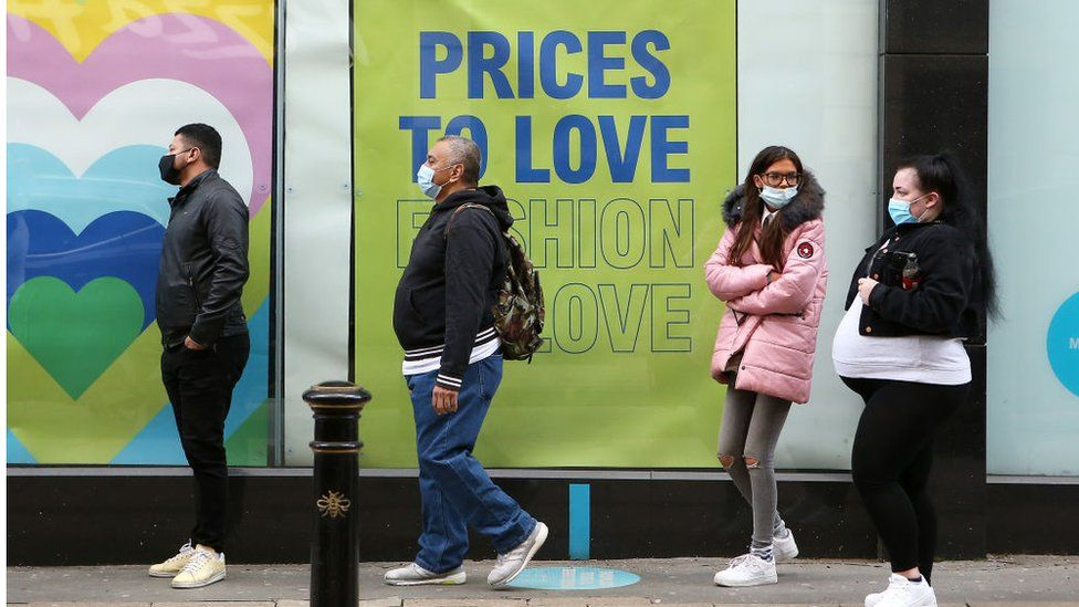 Shoppers queuing outside a shop in Manchester on 12 April