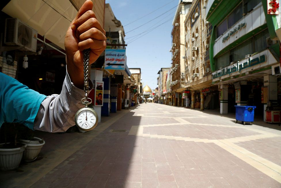 A man holds a pocket watch at noon, in front of an almost empty market near the Imam Ali shrine in Najaf, Iraq