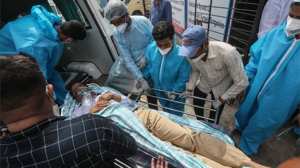 Health workers move a suspected COVID-19 patient outside the Vijay Vallabh COVID care hospital in the aftermath of a fire