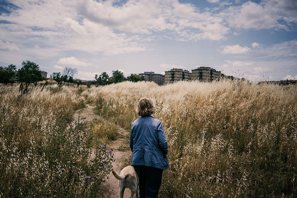 A lady stands in a field with a dog on a lead next to a residential