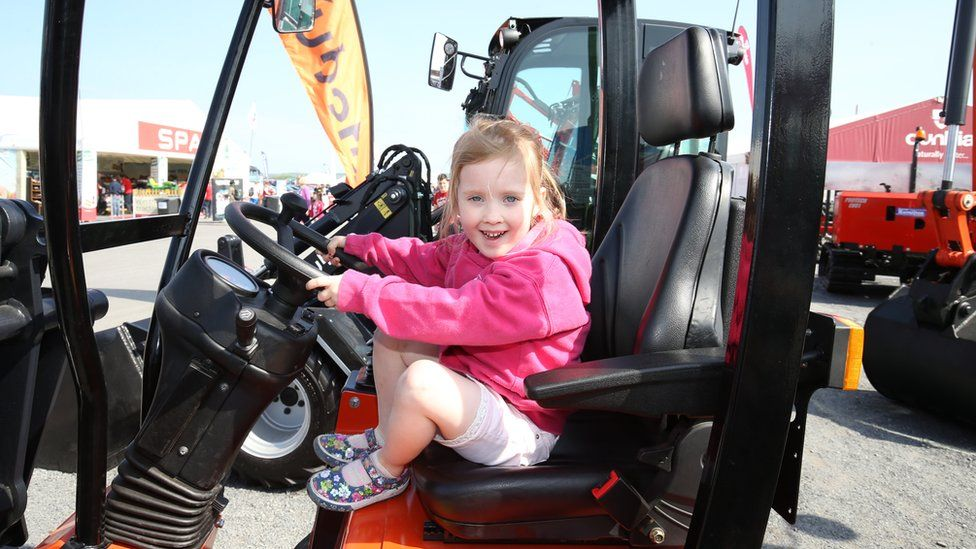 A girl sits in the cab of a digger at Balmoral Show