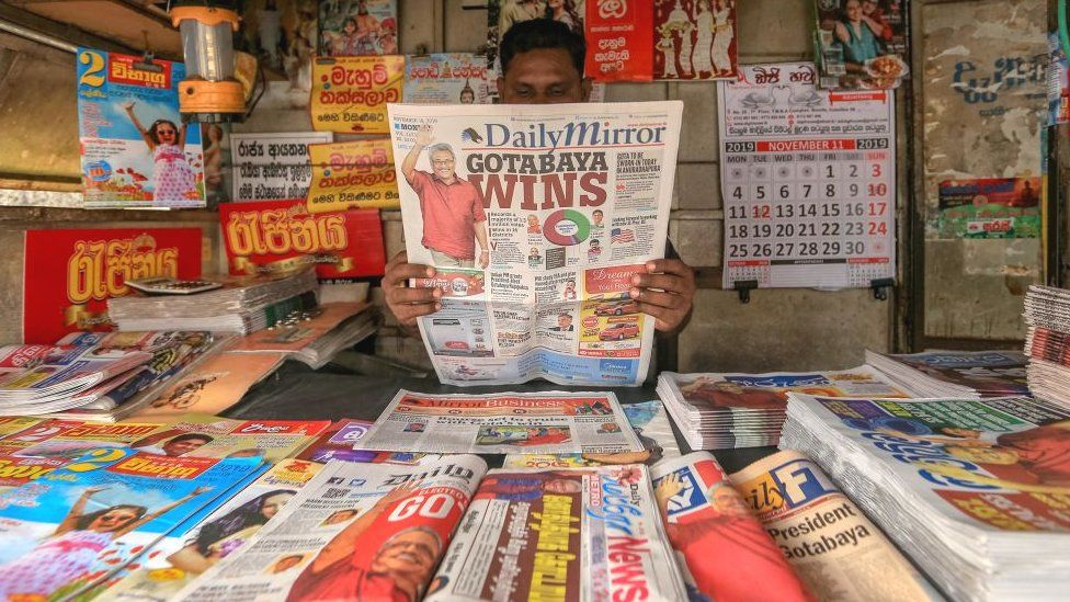 A Sri Lankan man reads a Sri Lankan newspaper headlining the victory of newly elected president Gotabaya Rajapaksa