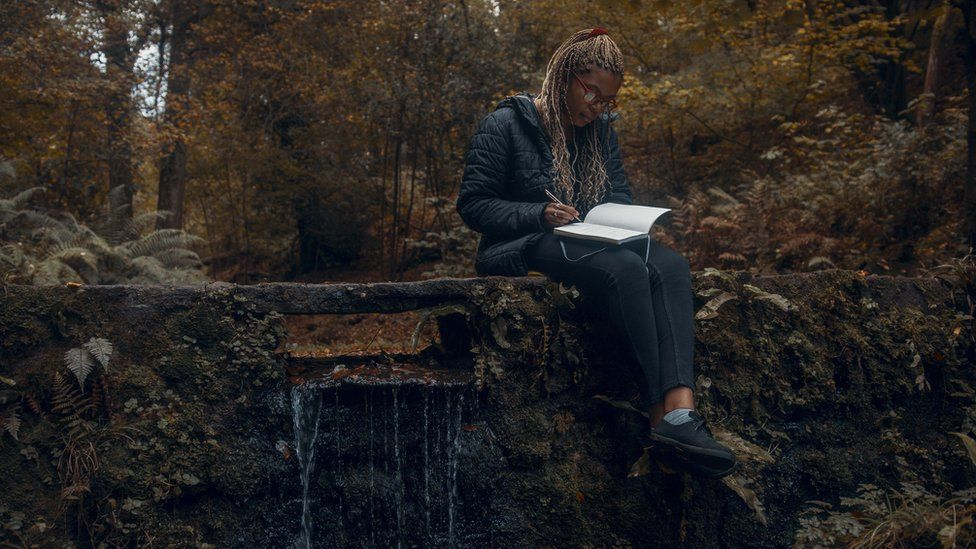 A woman writing in the forest
