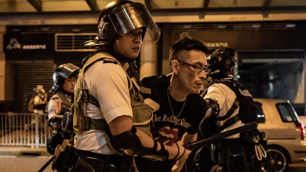 A protester is detained by police outside of Po Lam Station on September 5