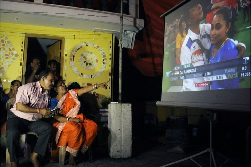 he parents of Indian gymnast Dipa Karmakar, Dulal Karmakar (L) and Gouri Karmakar (R) alongwith family members watch a projector screen in Agartala late August 14, 2016, as it shows the performance of Dipa in the vault finals of the gymnastics event at the 2016 Rio Olympic Games.
