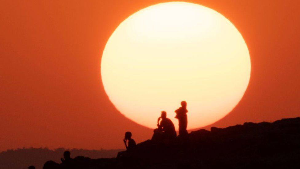 Ethiopian refugees who fled the Ethiopia's Tigray conflict watch the sunset on a hill at the Um Raquba refugee camp in Sudan's eastern Gedaref state - 12 December 2020