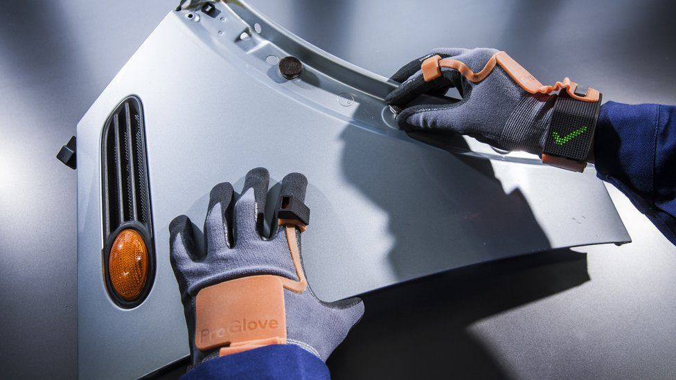 Worker attaching a nut to a car panel