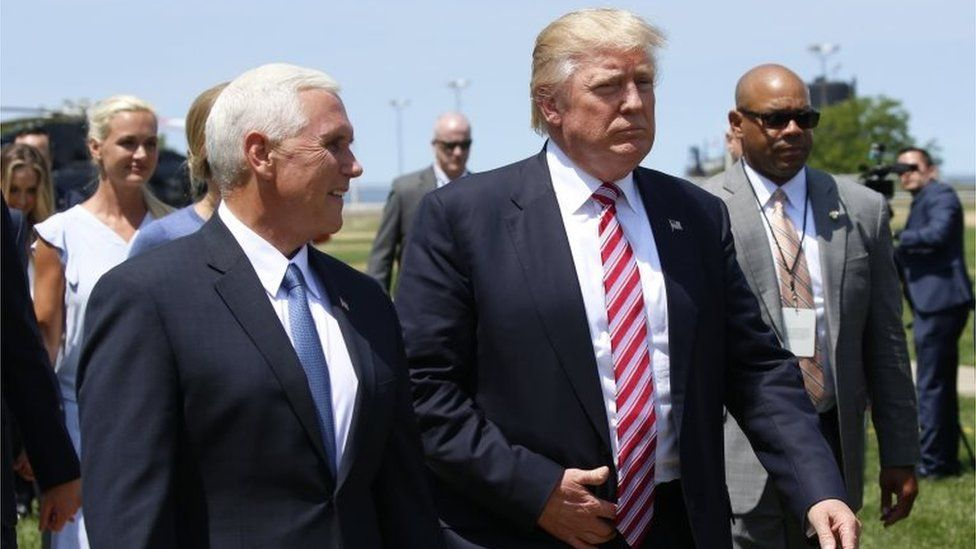 Donald Trump (R) walks with vice-presidential nominee Mike Pence (C) after arriving in Cleveland, Ohio, (20 July 2016)